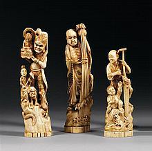 LOT DE TROIS OKIMONO en ivoire marin, représentant un oni en pied dressant une effigie de Bishamon en compagnie d'une fillette, drag...