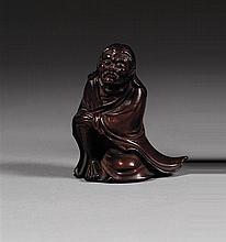 OKIMONO en bois laqué, représentant un rakan assis, vêtu d'un grand manteau, les yeux mi-clos et les mains réunies sur son genou dro...