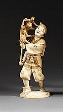 OKIMONO en ivoire rehaussé d'encre, représentant un sarumawashi accompagné de ses trois singes grimpés sur une perche surmontée d'un...