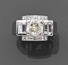 Bague chevalière ornée au centre d'un diamant taille brillant (DT) en chaton carré entouré de diamants baguettes. Monture en platine...