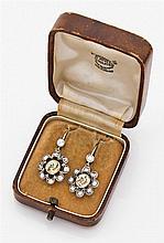 Paire de pendants d'oreilles marguerite ornés au centre d'un saphir jaune de forme ronde dans un entourage dentelé de diamants taill...