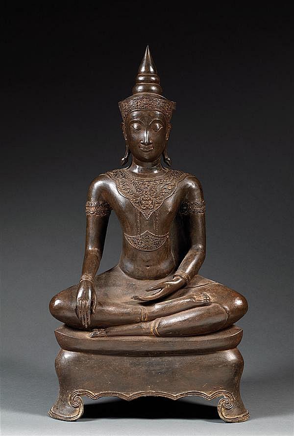 STATUE en régule de patine sombre, représentant le Bouddha Shakyamuni, assis en dhyanasana sur un socle triangulaire, la main droite en