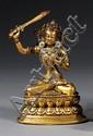 STATUETTE en cuivre doré et rehauts de laques rouge et bleu à l'imitation du corail et de la turquoise, représentant Manjushri assis...