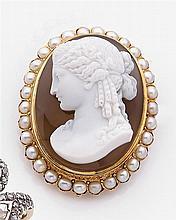 Broche camée Elle est ornée d'un camée sur agate blonde à deux couches représentant un profil de femme dans un entourage de demi-per...