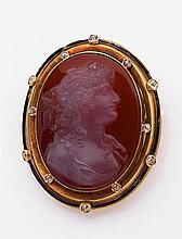 Broche camée cornaline Elle est ornée d'un camée sur cornaline de forme ovale, à portrait de jeune femme. Monture en or jaune émaill...