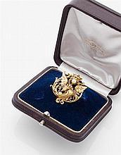 Paul TEMPLIER Années 1900 Broche chimère ailée en or jaune ajouré finement ciselé tenant dans sa gueule une perle et entourée de vol...