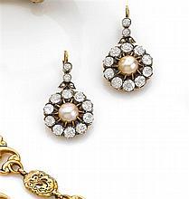 XIXe siècle Paire de boucles d'oreilles de forme ronde. Elles portent au centre une perle fine dans un entourage de diamants taille ...
