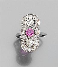 Années 1920 Longue bague en platine et or gris 18K ornée d'un saphir rose encadré de deux diamants (TA) dans un entourage de petits ...