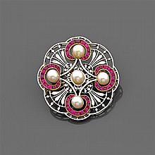 Années 1910 Broche ronde en platine et or gris 18K ajourée de fleurons et rehaussée de cinq perles fines dans des entourages de rubi...