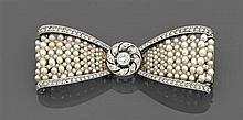 CARTIER Années 1920 Broche noeud papillon entièrement rehaussée d'une résille de perles fines. Au centre une rosace et deux bordures...