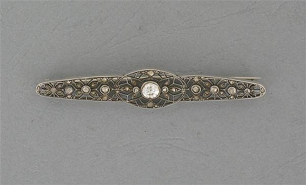 Broche Barrette en platine, ornée au centre d'un diamant rond taille brillant (TA) et de petits diamants taillés en rose. Poids brut...