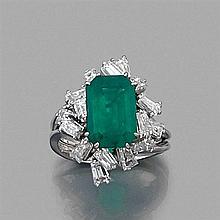 BAGUE ÉMERAUDE ET DIAMANTS Elle porte une émeraude rectangulaire en châton à griffes dans un riche entourage de diamants baguettes e...