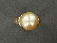 BAGUE PERLE DE CULTURE GOLD La grosse perle de culture de ton gold est supportée par une monture jonc moulurée en or jaune 18K. Trav...