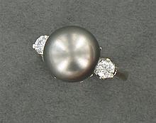 BAGUE PERLE DE CULTURE Elle est ornée d'une perle de culture grise de Tahiti, encadrée par deux diamants taille brillant. Monture en...