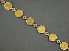 BRACELET MONNAIES Il se compose de onze monnaies de 10 francs en or jaune réunies par des motifs ronds Poids brut : 45,6 gr Longueur...