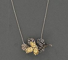 PENDENTIF  en or jaune 18K et argent , représentant une branche de noisetier et trois noisettes en or jaune travaillé, les feuilles serties de petits diamants taillés en rose. La chaîne également en or gris 18K.