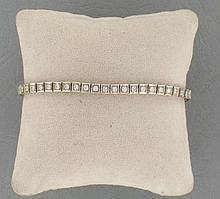 BRACELET LIGNE  en or gris 18K orné de diamants en chatons carrés sertis à griffes.