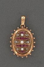 PENDENTIF OVALE OUVRANT  en or rose 18K, orné de motifs géométriques sertis alternativement de rubis taille ancienne et petits diamants taillés en rose (un manque), 3 demi-perles au centre.