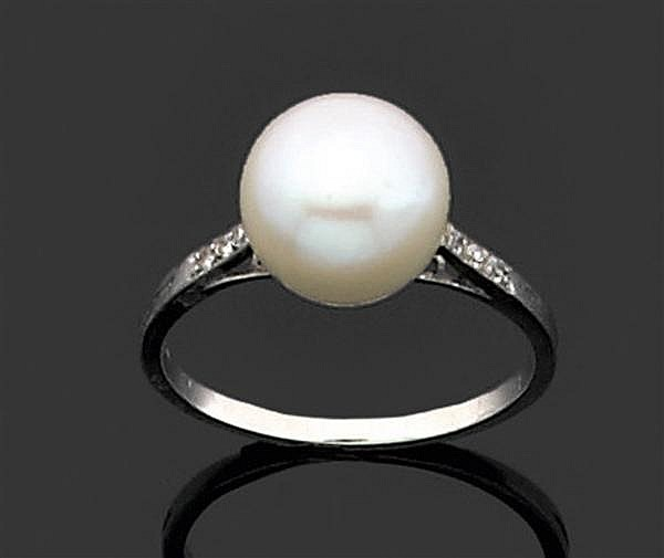 RENé BOIVIN Années 1910 Bague  en platine, ornée au centre d'une perle fine de forme bouton épaulée de petits diamants taille brilla...