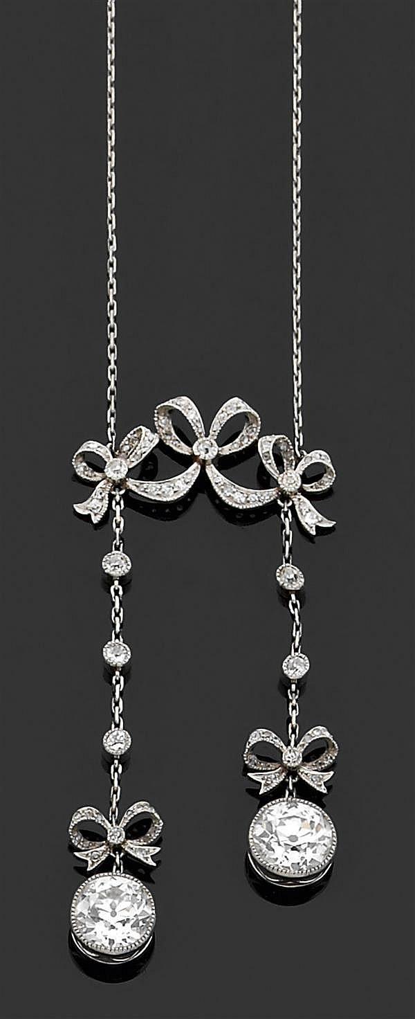 Négligé en platine, composé d'un motif de trois nœuds de rubans sertis de petits diamants retenant en pampille deux diamants taille ...
