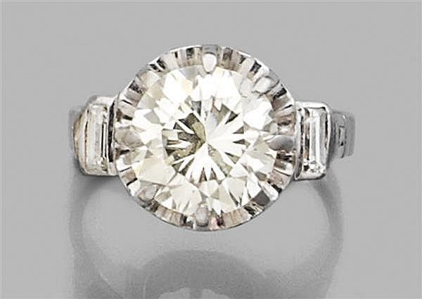 Bague diamant solitaire en platine, ornée d'un diamant taille brillant en chaton à griffes épaulé de diamants baguette. Travail fran...