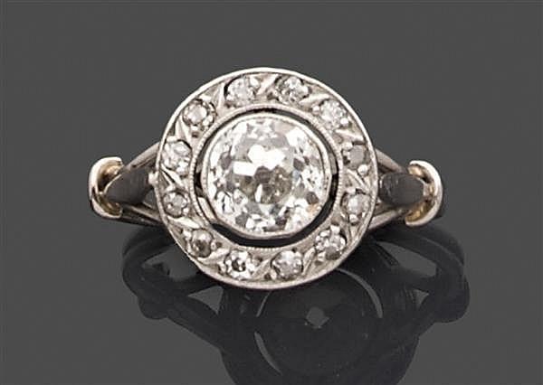 Bague en platine, ornée au centre d'un diamant taille brillant (TA) en serti clos entouré de petits diamants. Travail des années 191...