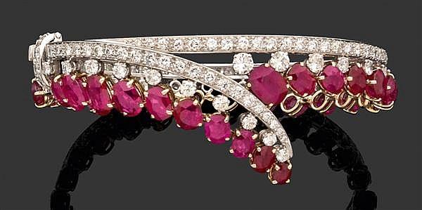 Bracelet rigide ouvrant en forme de lien noué constitué d'un tour de bras rigide serti de diamants sur platine bordé d'une frange de...