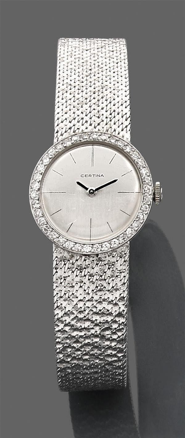 CERTINA Années 1970 Montre de dame en or gris, boîtier rond entouré de diamants taille brillant.Tour de bras en or gris matricé. Mou...
