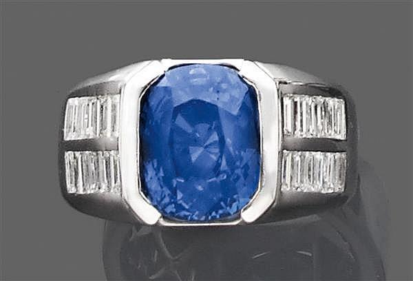 Bague saphir solitaire en or gris, ornée d'un saphir coussin et encadré de diamants baguette disposés en damier. Poids brut : 13,5 g...