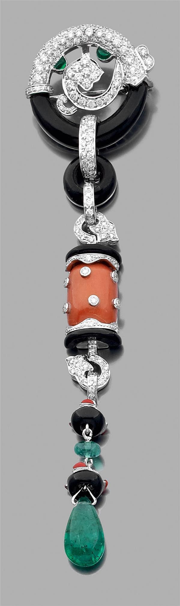 Pendentif broche en or gris, composé de motifs géométriques sertis d'onyx, de corail et de petits diamants, retenant une émeraude ca...