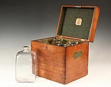 SHIP CAPTAIN'S LIQUOR CASE - Mid 19th c. Oak Case with four green felt lined compartments, cradling original handblown square, clear gin bottles with flared rims having spouts, no stoppers, unground pontils. Label ins..
