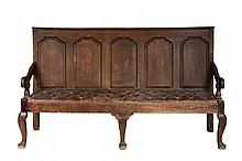 18TH C OAK BENCH - English Oak Hall Bench, having five raised and paneled back, molded top rail, elbow arm rests on urn turned supports, three simple cabriole front legs with pad feet, square back legs, later oxblood ...