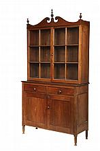 STEPBACK CUPBOARD - Country Sheraton Two-Part Walnut Cupboard, found in Maine, with broken arch pediment having beehive finials and applied bull's-eyes, the upper cabinet with glass doors having six lights each over t..