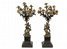 PAIR OF FRENCH BRONZE CANDELABRUM - Second Empire five stem parcel gilt and ebonized bronze candelabrum with slate and green marble bases, featuring opposing figures of seated putti supporting volutes from which emana...