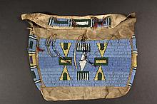 SIOUX BEADED HIDE POSSIBLE BAG - Late 19th c. Deer Hide Bag in two-sided form with shallow flap, sinew sewn body with lane-stitched beadwork having a pale blue field, dark green, yellow and white forms, decorated with...