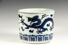 CHINESE PORCELAIN POT - A Large Cylindrical Pot with Blue & White Decoration of a Celestial Dragon in pursuit of a Phoenix among flaming clouds, a row of tablets along the lower edge, slightly recessed raw foot. 6 1/2...