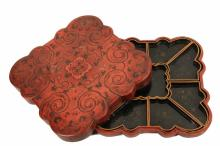 LIDDED CHINESE LACQUERED SWEETMEAT BOX - Early 19th c. Heavy Red Lacquered Papier Mache Box with Lingxhi shaped and engraved corners, having black and silver painted decoration of scrolls, leaves and moths, a raised c...