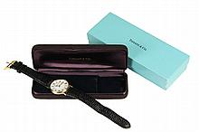 GENT'S WRISTWATCH - 14K Yellow Gold Round Head Tiffany & Co. Wristwatch with box, with date time movement, Swiss made, water resistant, engraved presentation to back of case, black textured leather Likeo band; 9