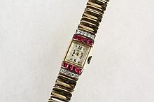 LADY'S WRISTWATCH - Tiffany & Co. 14K Yellow Gold, Ruby and Diamond Art Deco Wristwatch in original Tiffany & Co. box, with rectangular head flanked by two rows of baguette rubies and round diamonds, 14K yellow gold l..
