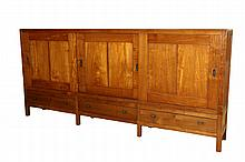 PLANTATION CABINET - Long Low Cabinet in solid teak, 20th c., unmarked, with three sliding panel door front, each with vertical incised centerline and having brass pocket handles, concealing single shelf interior, set...