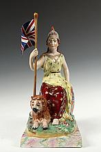 STAFFORDSHIRE FIGURE - English Porcelain Allegorical Figure of Brittania Enthroned, circa 1820, with lion reclining alongside, the woman warrior in yellow and crimson dress with gilt detailing, wearing a Greek helmet,...