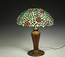 STAINED GLASS TABLE LAMP - Vintage Renaut Spelter Base, 1920's vintage, in bronze finish, two electric sockets with pull chains, having a 1970's vintage arched dome leaded slag glass shade with polychrome blossoms and.