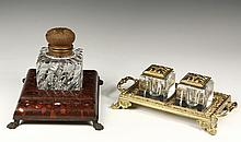 (2) GILDED AGE INKWELLS - Including: French Single Bottle Stand with ornate cast bronze domed hinged cap, heavy square swirled crystal bottle, oxblood marble plateau with pen notch, set on bronze lion-paw footed plate...