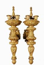 PAIR OF MONUMENTAL GILT BRONZE ARCHITECTURAL SCONCES - Elizabethan Revival, American Gilded Age, made by Caldwell, in the form of a four socket torchiere supported by a scroll arm with substantial wall plate, roughly ...