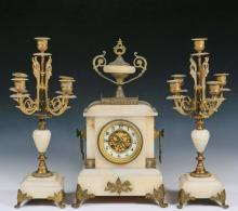 (3 PC) FRENCH MANTEL GARNITURE - Pale Gold Alabaster and Bronze Set of Clock and Pair of Five-Stem Candelabrum, by Japy Freres, in Classical Revival style, having an urn atop the clock, enamel and gilt dial, bosses wi...
