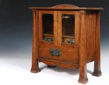 ARTS & CRAFTS SMOKING CABINET - Tabletop Cabinet in Golden Oak, circa 1910, with overhanging molded edge top having a center dome, small drawers with compartments above are behind a pair of wavy glass doors that fold ...