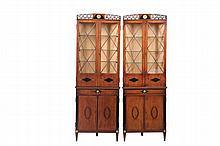 PAIR OF CORNER CUPBOARDS - Circa 1900 Diminutive Mahogany Cabinets in the Greek style, with reticulated black painted crest featuring wheat fronds and a gilt metal medallion of Artemis, two glass doors below have diam...