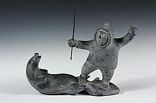 MOSES AUPALUKTUK (aka MOSESEE; AULPALUTAQ; RED) Born: 1924, Inukjuak, Died: 1983, Puvirnituq. Gray Stone Inuit Carving of Hunter Standing Over Seal, both arms raised, metal harpoon in right hand, signed on underside a...