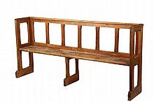 SCHOOL BENCH - Early American School Bench in pine, with back and arms, in open chamfered frame, having a bullnose slab seat, mortise and tenon wood pegged construction, shoe foot. 18