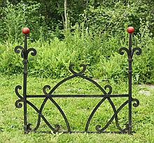 IRON ARCHITECTURAL DETAIL - Roofline Motif, having double fleur-de-lis motif with the ball finials in red paint, the remainder in black, constructed of substantial riveted strapwork, with lower brackets to provide sup...